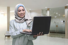 Young asian muslim woman using laptop while standing Stock Photos