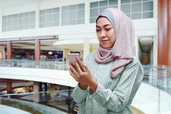 Young asian muslim woman in veil using mobile phone Stock Image
