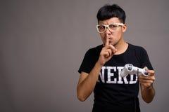 21c9e49c8459 Young Asian nerd man wearing eyeglasses against gray background. Studio shot  of young Asian nerd