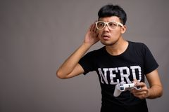21c9e49c8459 Young Asian nerd man wearing eyeglasses against gray background. Studio shot  of young Asian nerd