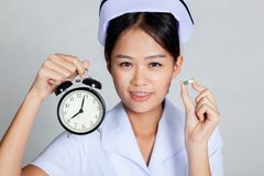 Young Asian nurse with clock and capsule Royalty Free Stock Photography