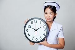 Young Asian nurse with a clock Stock Image