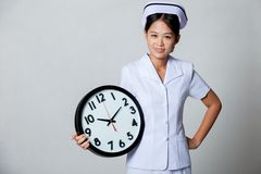 Young Asian nurse with clock Royalty Free Stock Image
