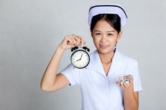 Young Asian nurse with clock and pills on her palm hand Stock Images