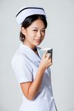 Young Asian nurse with a cup of coffee Stock Photography