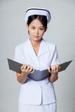Young Asian nurse with a folder Royalty Free Stock Images