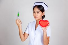 Young Asian nurse hold syringe and red heart Stock Photo