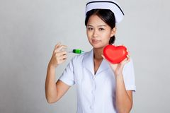 Young Asian nurse hold syringe and red heart Royalty Free Stock Images