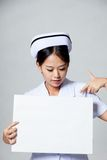 Young Asian nurse point down to blank sign Stock Photography