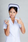 Young Asian nurse point at pills Stock Photo