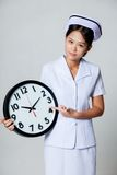 Young Asian nurse point to a clock Royalty Free Stock Photo