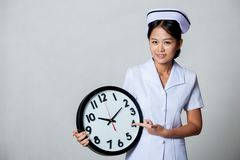 Young Asian nurse point to a clock Stock Images