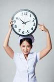 Young Asian nurse point to clock over her head Stock Photos