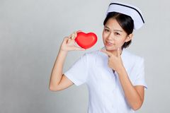 Young Asian nurse point to red heart Stock Images