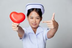 Young Asian nurse point to red heart Royalty Free Stock Photos