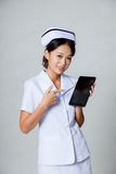 Young Asian nurse point to a tablet pc Stock Image