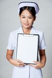 Young Asian nurse show blank paper on clipboard Royalty Free Stock Photography