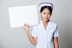Young Asian nurse show blank sign on her shoulder Royalty Free Stock Image