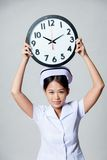 Young Asian nurse show a clock over her head Royalty Free Stock Images