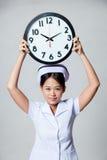 Young Asian nurse show a clock over her head Stock Photos