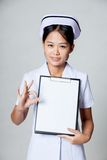 Young Asian nurse show OK  with blank paper on clipboard Stock Photography