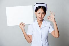 Young Asian nurse show OK with blank sign on her shoulder Royalty Free Stock Image