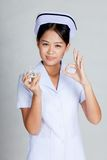 Young Asian nurse show OK with some pills. On gray background stock photos