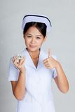 Young Asian nurse show thumbs up with some pills. On gray background royalty free stock images