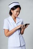 Young Asian nurse surfing net with tablet pc Stock Photo