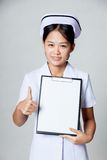 Young Asian nurse thumbs up with blank paper on clipboard Stock Photos
