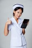Young Asian nurse thumbs up with a tablet pc Royalty Free Stock Image
