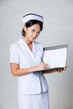 Young Asian nurse work on a folder look at camera Royalty Free Stock Photography
