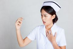 Young Asian nurse worry look at  thermometer Stock Photography