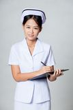 Young Asian nurse writing on a clipboard and smile Royalty Free Stock Photos