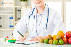 Young asian nutritionist doctor writing diet plan. Healthy eating Stock Photos