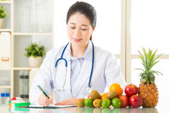 Young asian nutritionist doctor writing diet plan. Healthy eating Royalty Free Stock Photos