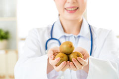 Young asian nutritionist holding kiwis. Healthy eating royalty free stock image