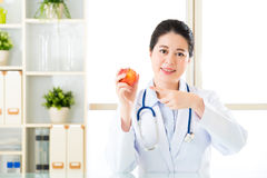 Young asian nutritionist recommend eating apple Royalty Free Stock Image