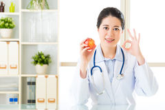 Young asian nutritionist recommend eating apple and ok sign Royalty Free Stock Image