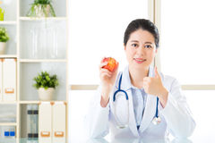 Young asian nutritionist recommend eating apple and thumbs up Stock Photo