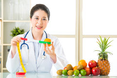 Young asian nutritionist recommend eating fruits Royalty Free Stock Images