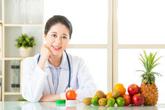 Young asian nutritionist recommend eating fruits Royalty Free Stock Photography