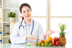 Young asian nutritionist recommend eating fruits Royalty Free Stock Photos