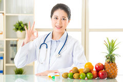 Young asian nutritionist recommend eating fruits and ok sign Royalty Free Stock Image