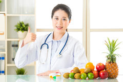 Young asian nutritionist recommend eating fruits and thumbs up Royalty Free Stock Image