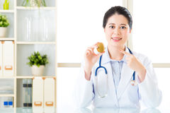 Young asian nutritionist recommend eating kiwi Royalty Free Stock Photography