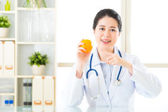 Young asian nutritionist recommend eating orange Royalty Free Stock Photography
