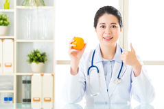 Young asian nutritionist recommend eating orange and thumbs up Royalty Free Stock Images