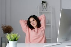 Young asian office woman relaxing while working with computer at Royalty Free Stock Photo