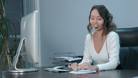 Young asian operator talking with customer in international call center Royalty Free Stock Photo